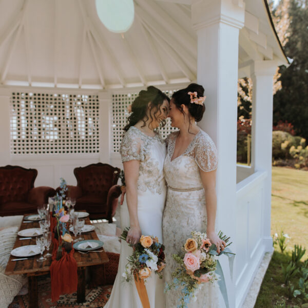 Two brides kiss in pavilion at Hayne House