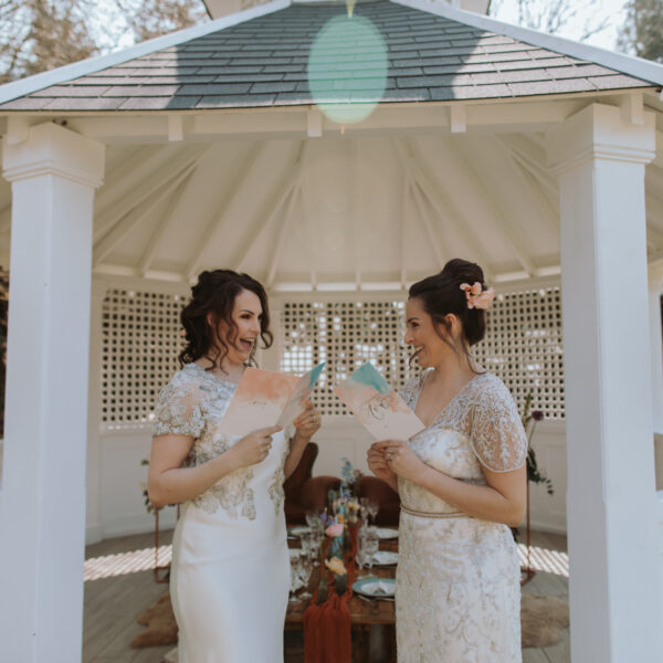 Two brides read vows to each other in Pavilion at Hayne House