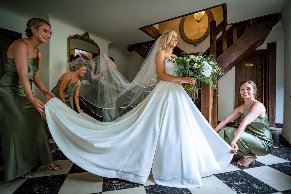 bridesmaids preparing bride's dress at Hayne House