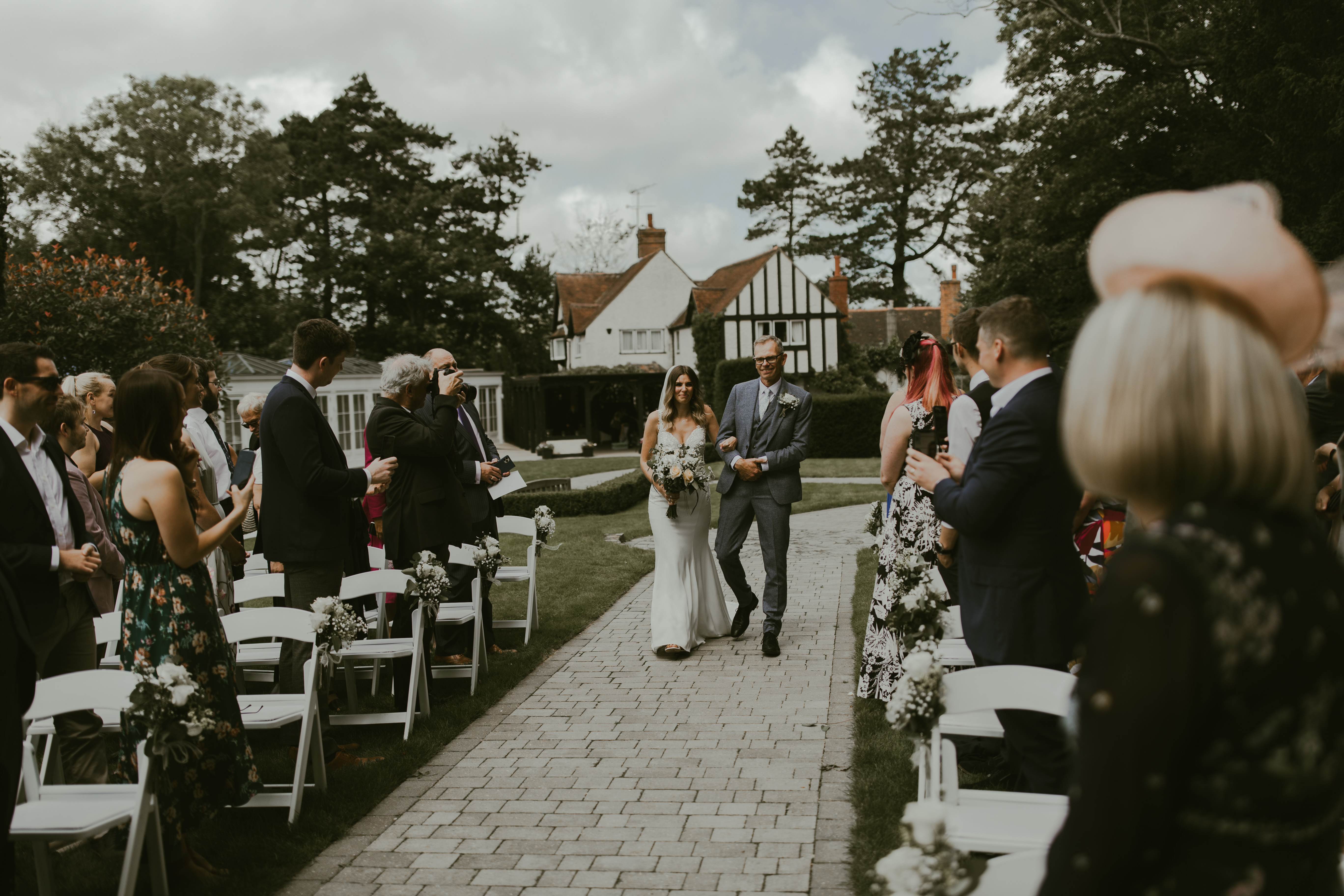 Bride being walked down paved aisle at Hayne House