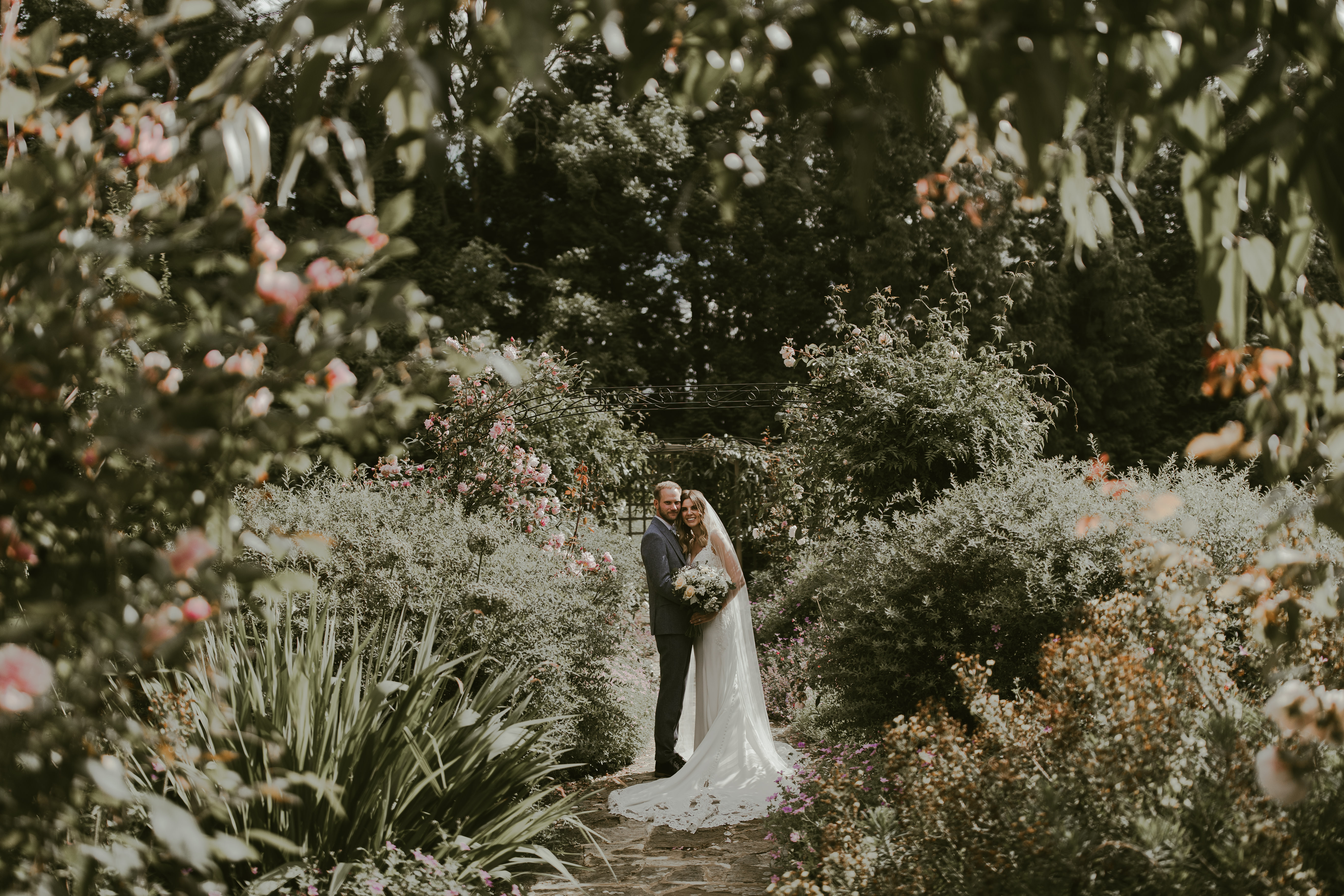Married couple pose for photo surrounded by bushes at Hayne House