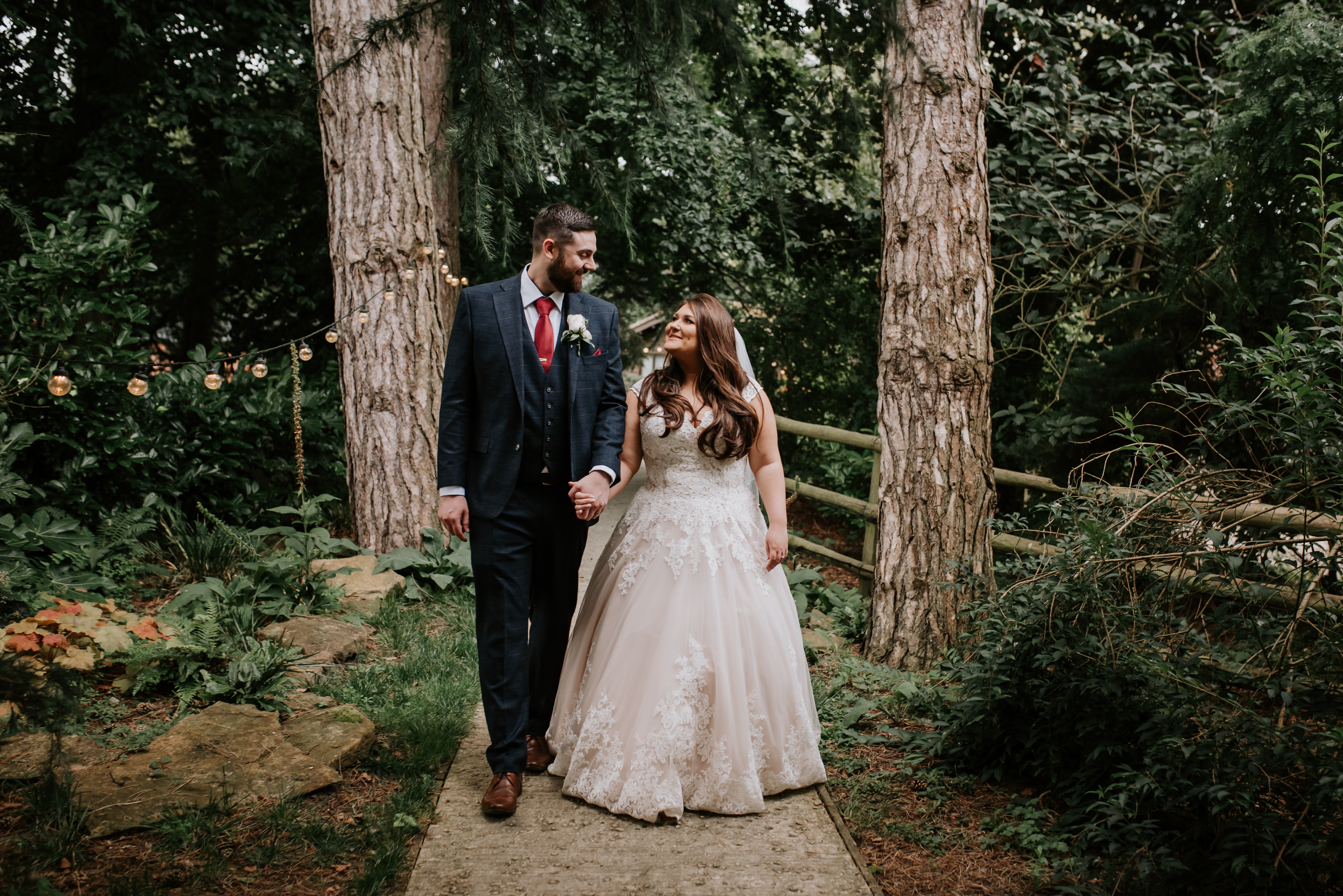 Married couple walk through woods at Hayne House