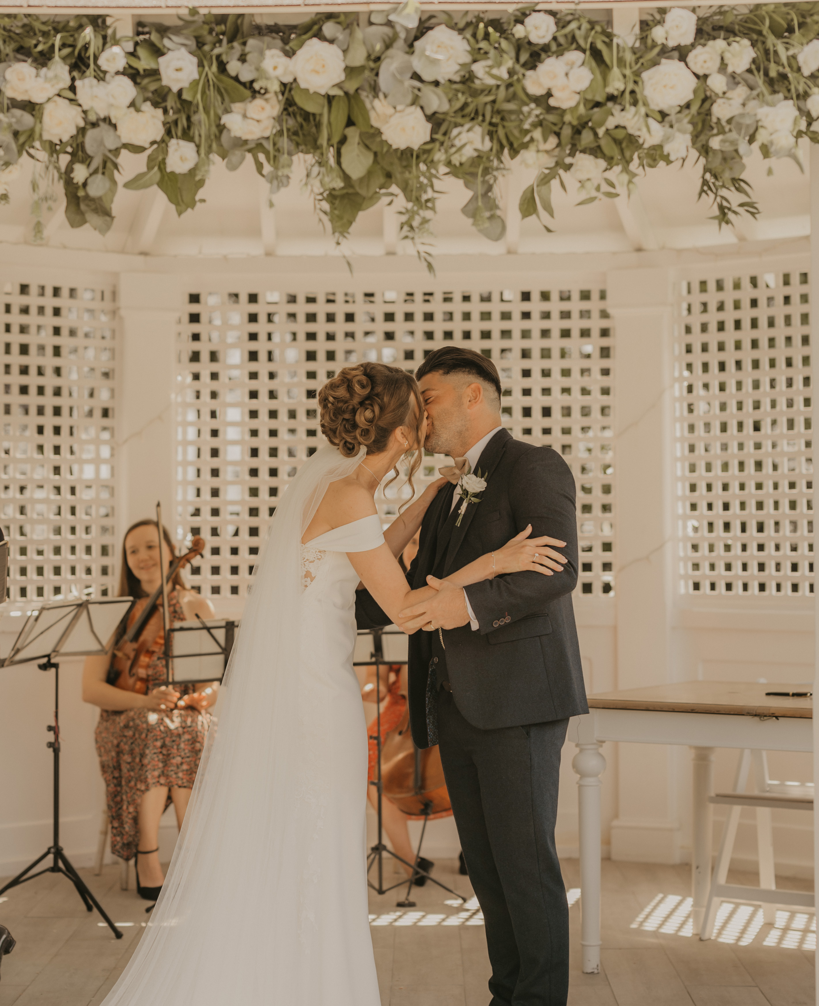 Married couple kissing as band play behind them   Hayne House
