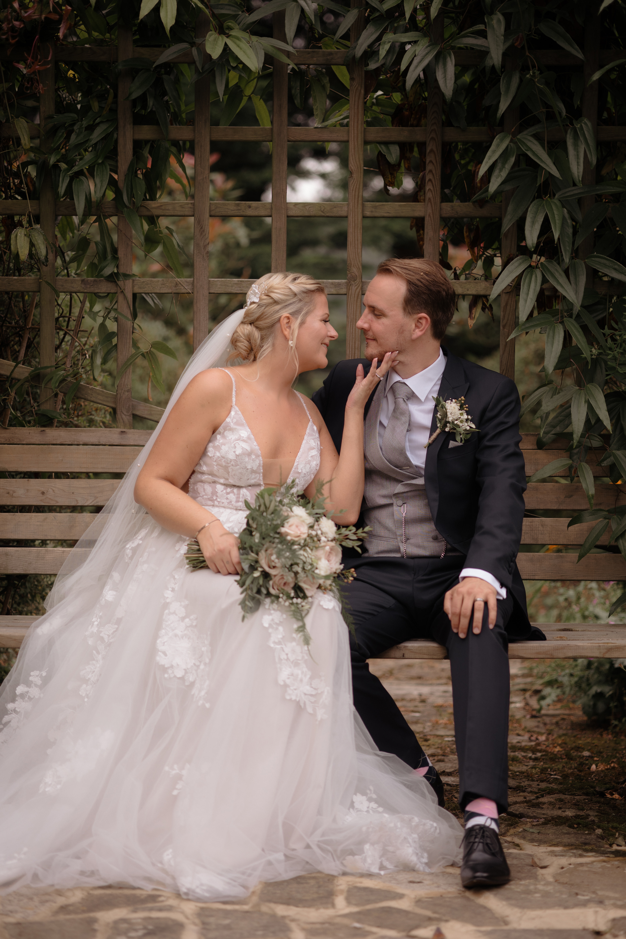 Married couple sit on bench about to kiss at Hayne House