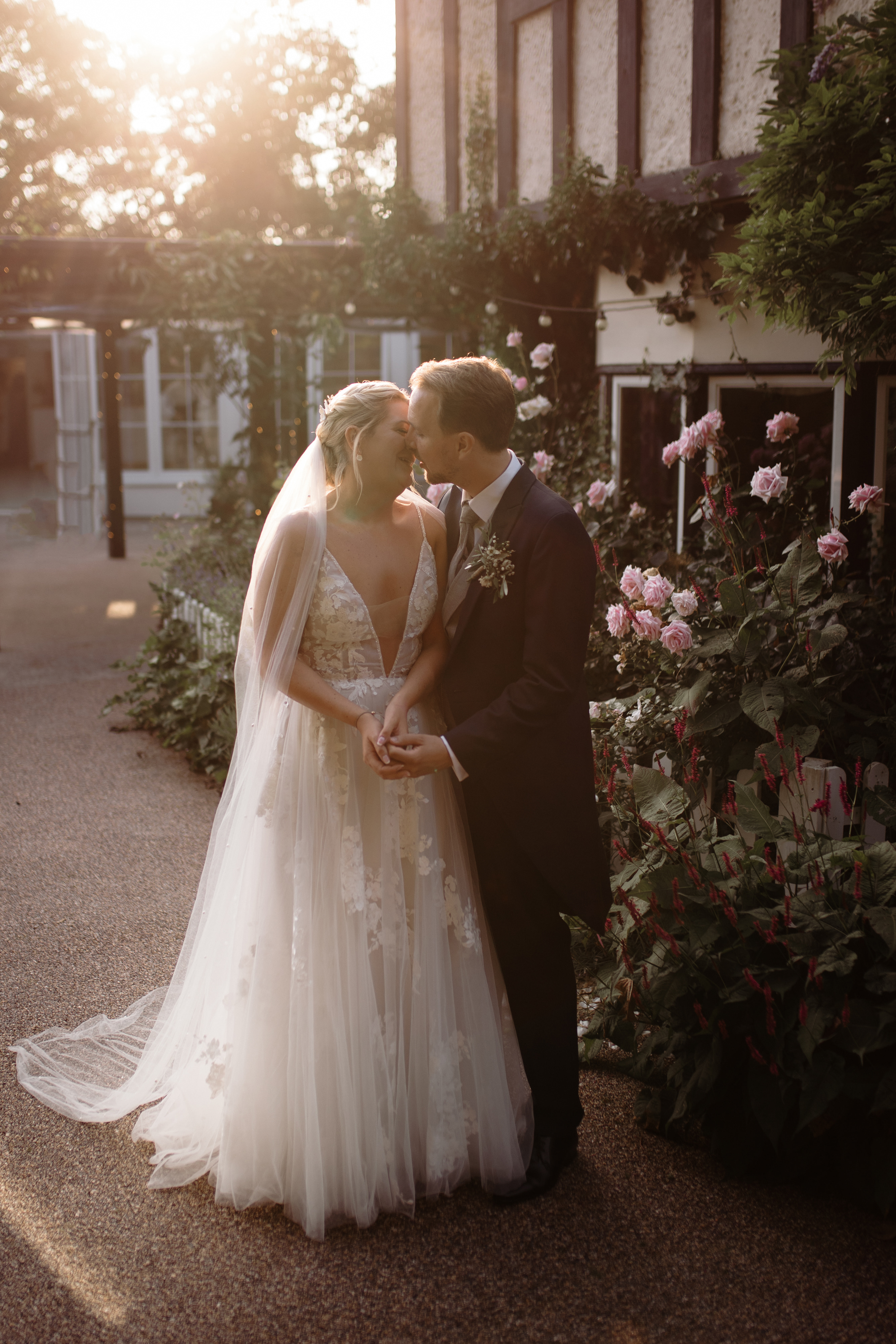Married couple kiss by rose bush at Hayne House