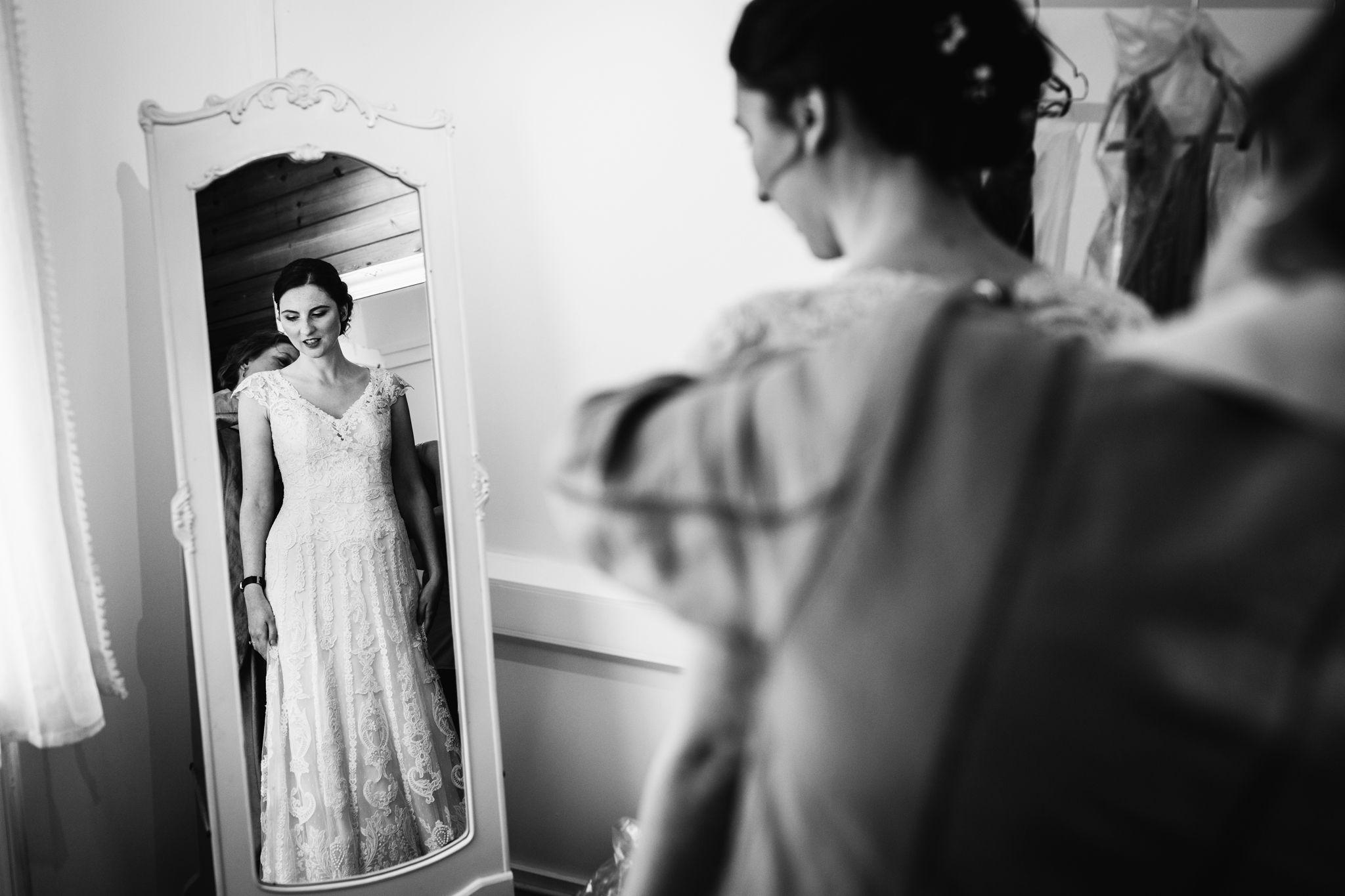 Bride putting on wedding dress in white mirror at Hayne House